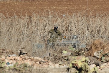 Bryan MacCormac   At the Edge  of the West Bank Village of Faqqua, an Israeli Soldier Watches from the Other Side of the Green Line